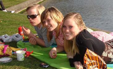 Tre musikkstudentar som nyter sola i Bergen.